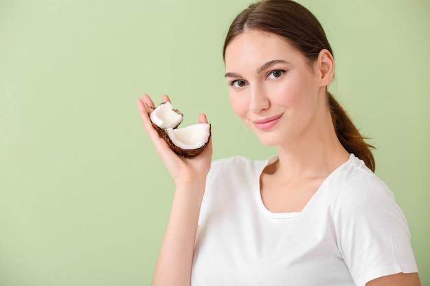 Mulher jovem e bonita com coco verde