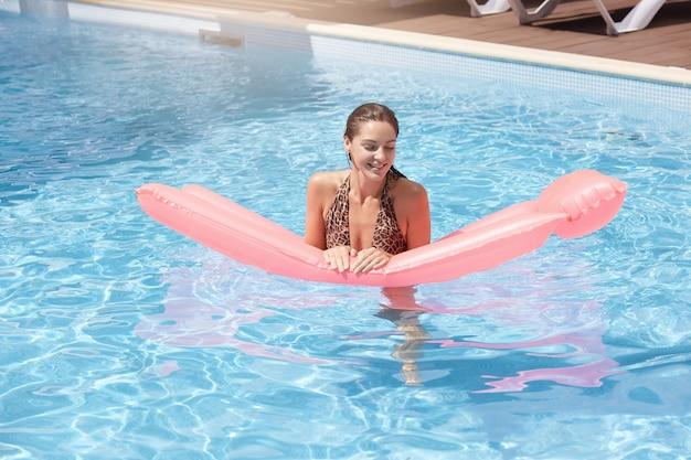 Mulher jovem e bonita com colchão inflável rosa flutuando na piscina