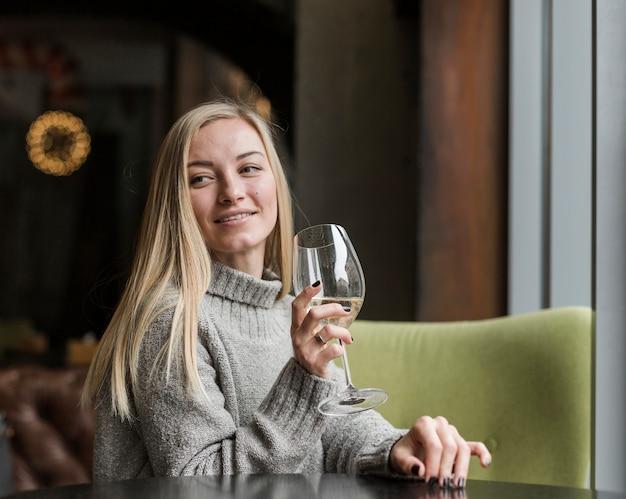Mulher jovem e bonita com copo de vinho, olhando para longe