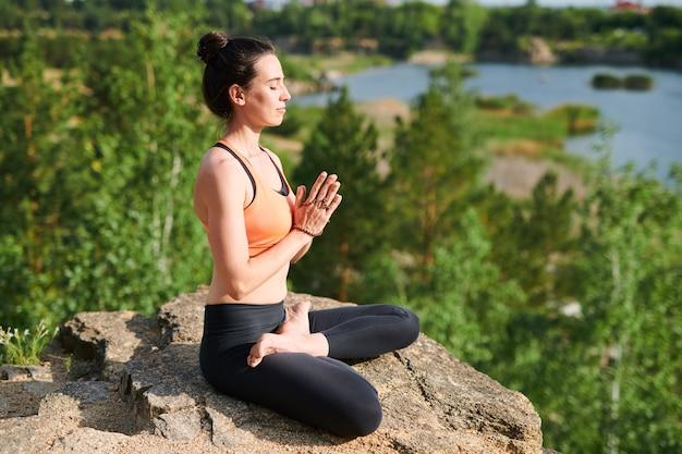 Mulher jovem e bonita com coque de cabelo concentrado em pensamentos durante a meditação nas montanhas