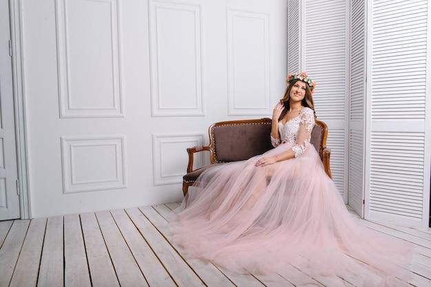 Mulher jovem e bonita com coroa de flores na cabeça e vestido rosa posando no estúdio branco