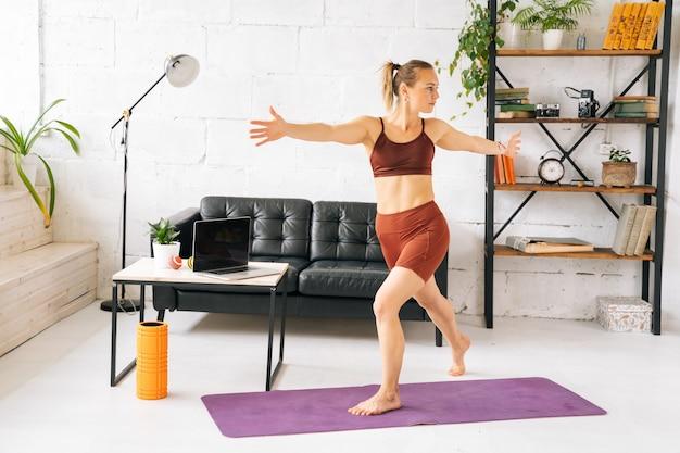 Mulher jovem e bonita com corpo atlético perfeito, vestindo roupas esportivas, malhando em pé descalço na esteira de exercícios. conceito de estilo de vida saudável e atividade física em casa.