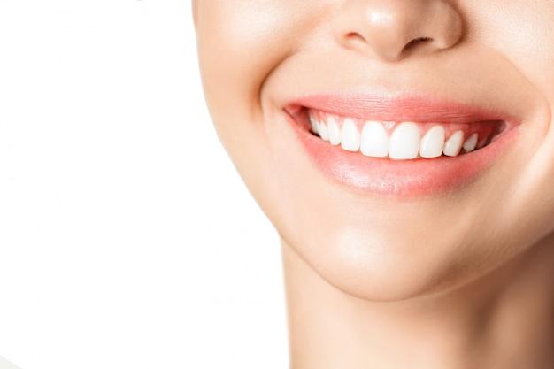 Mulher jovem e bonita com dentes saudáveis na parede branca.