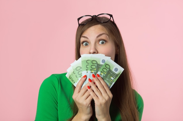 Mulher jovem e bonita com dinheiro do euro em fundo rosa