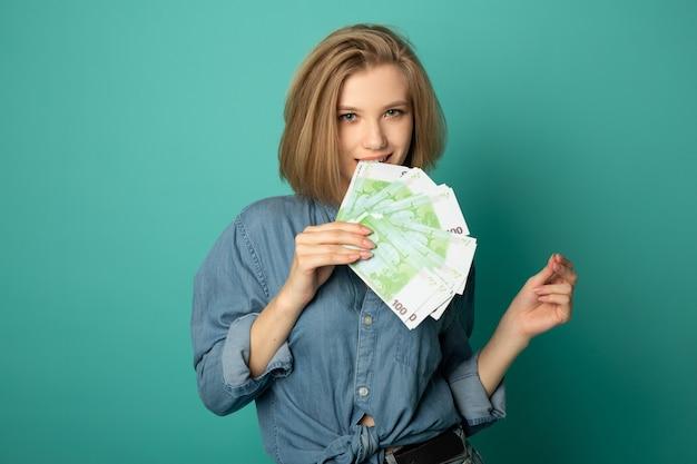 Mulher jovem e bonita com dinheiro euro nas mãos Foto Premium