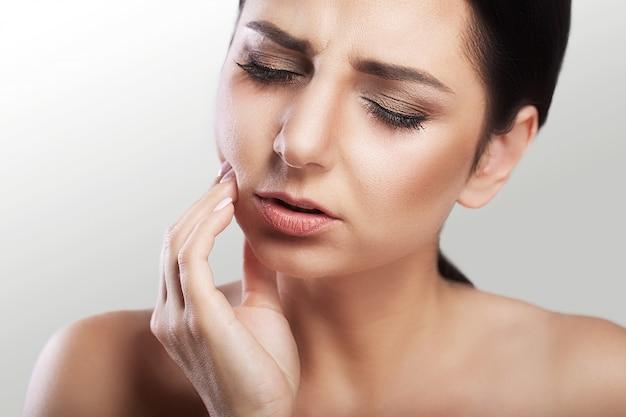 Mulher jovem e bonita com dor de dente, cárie, problemas dentários, sensações dolorosas no rosto, maquiagem linda.