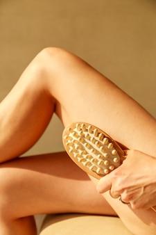 Mulher jovem e bonita com escova de massagem anti celulite