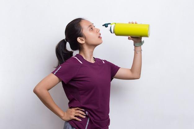 Mulher jovem e bonita com esportes asiáticos bebendo água após o treino em fundo branco Foto Premium