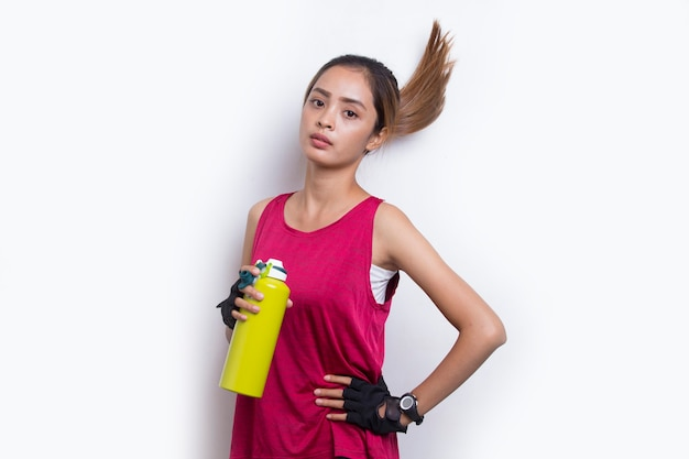 Mulher jovem e bonita com esportes asiáticos bebendo água após o treino em fundo branco