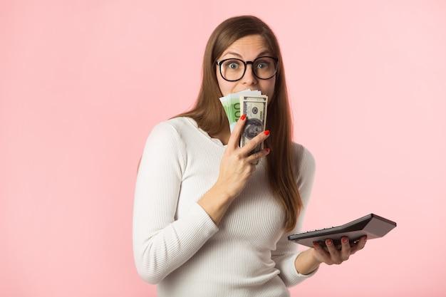 Mulher jovem e bonita com euros e dólares em fundo rosa