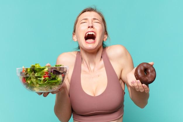 Mulher jovem e bonita com expressão de raiva no esporte, segurando um sanduíche e uma rosquinha