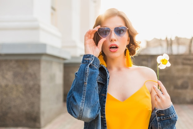 Mulher jovem e bonita com expressão de rosto surpreso, emocional, emoção chocada, vestindo roupas elegantes, jaqueta jeans, blusa amarela, segurando uma flor, verão ensolarado, óculos de sol azuis engraçados da moda