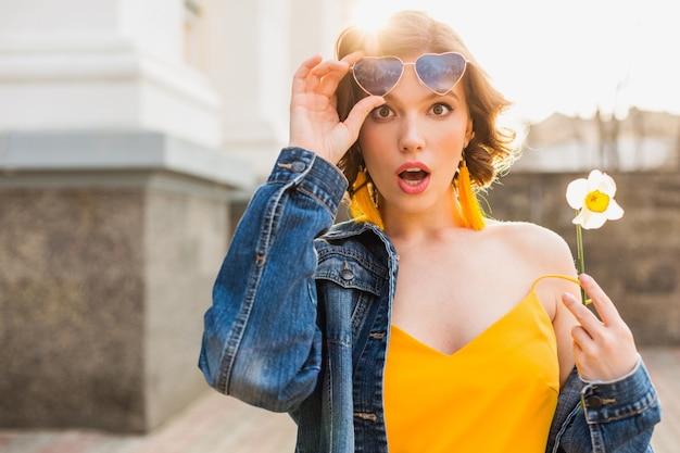 Mulher jovem e bonita com expressão de rosto surpreso, emocional, emoção chocada, vestindo roupas elegantes, jaqueta jeans, blusa amarela, segurando uma flor, verão ensolarado, óculos de sol engraçados da moda