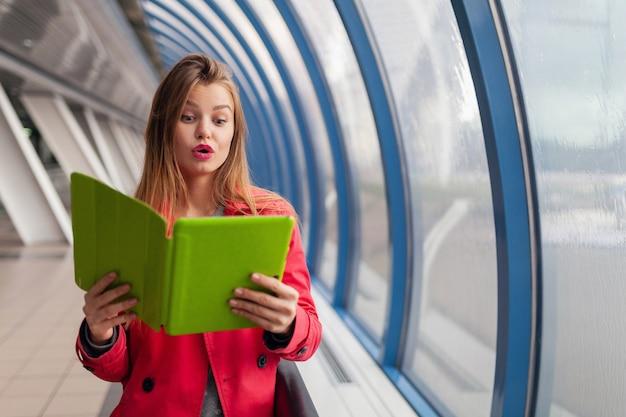 Mulher jovem e bonita com expressão de surpresa segurando um tablet laptop em um prédio urbano