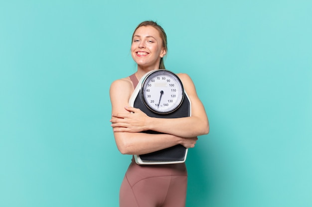 Mulher jovem e bonita com expressão feliz e segurando uma balança