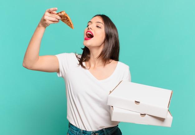 Mulher jovem e bonita com expressão feliz e segurando uma pizza