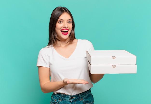 Mulher jovem e bonita com expressão feliz segurando pizzas para levar e segurando pizzas para levar