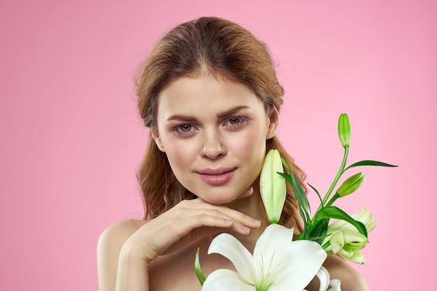 Mulher jovem e bonita com flor de lírio branco, posando em um espaço rosa, romântica imagem concurso