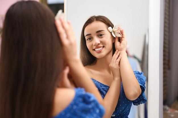 Mulher jovem e bonita com flor de orquídea se olhando em um grande espelho dentro de casa