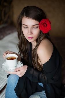 Mulher jovem e bonita com flor no cabelo. a garota se senta na cama e bebe chá
