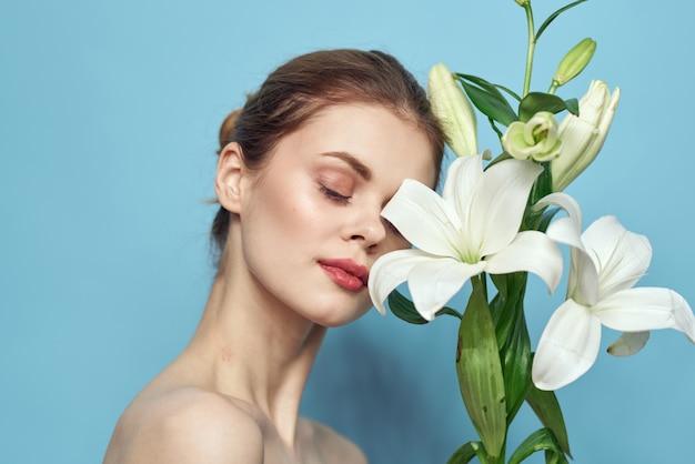 Mulher jovem e bonita com flor posando no estúdio em uma parede azul clara, romântica imagem concurso, retrato de mulher