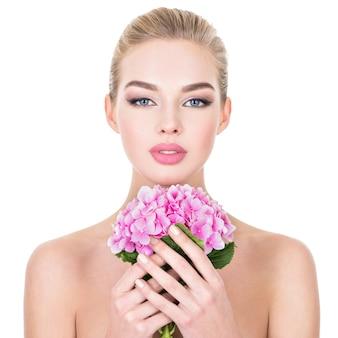 Mulher jovem e bonita com flores perto do rosto.