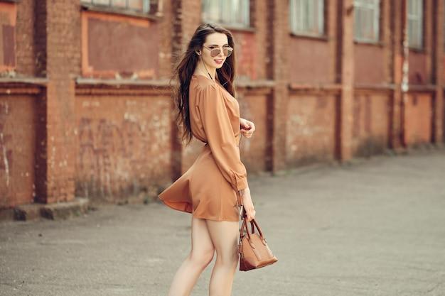 Mulher jovem e bonita com fones de ouvido andando na calçada