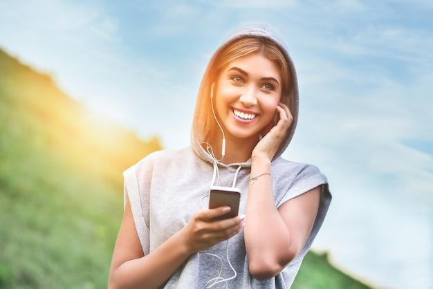 Mulher jovem e bonita com fones de ouvido feliz depois de uma boa corrida no parque da cidade
