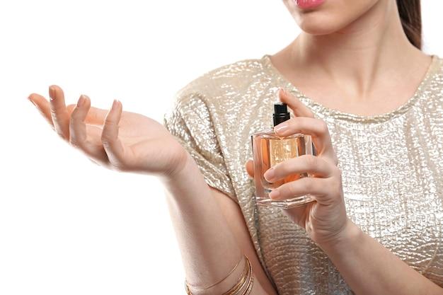 Mulher jovem e bonita com frasco de perfume na superfície branca