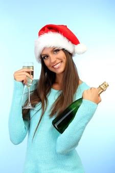 Mulher jovem e bonita com garrafa e taça de champanhe,