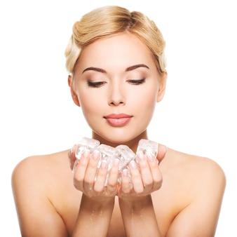 Mulher jovem e bonita com gelo nas mãos. conceito de cuidados com a pele. isolado no branco.