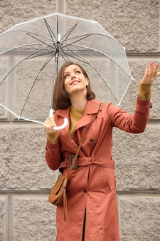 Mulher jovem e bonita com guarda-chuva ao ar livre em dia chuvoso