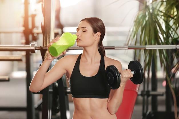 Mulher jovem e bonita com halteres bebendo batido de proteína na academia