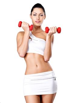 Mulher jovem e bonita com halteres - conceito de estilo de vida saudável.