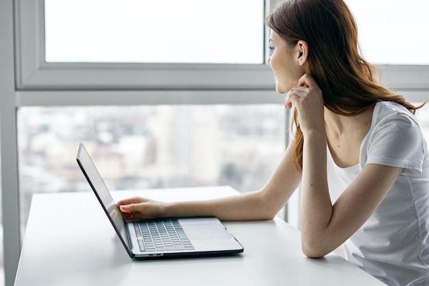 Mulher jovem e bonita com laptop em camiseta branca no fundo da janela
