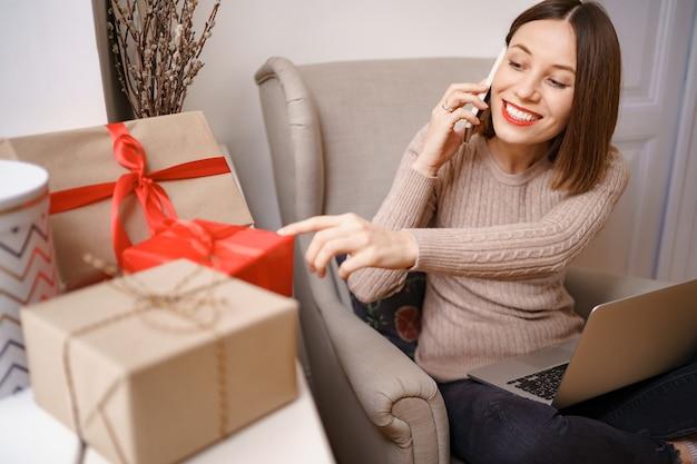 Mulher jovem e bonita com laptop falando no celular enquanto está sentado em uma poltrona confortável