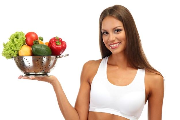 Mulher jovem e bonita com legumes em uma peneira, isolada no branco