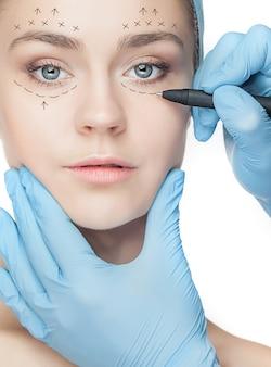 Mulher jovem e bonita com linhas de perfuração no rosto antes da operação de cirurgia plástica. esteticista tocando o rosto da mulher.