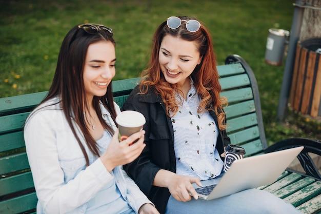 Mulher jovem e bonita com longos cabelos vermelhos conversando com sua amiga enquanto está sentado do lado de fora no banco com um laptop nas pernas.