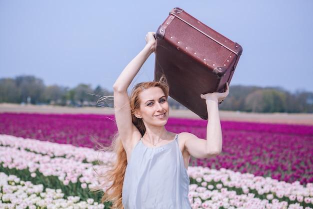 Mulher jovem e bonita com longos cabelos vermelhos usando vestido branco em pé com bagagem no campo de tulipa colorida.