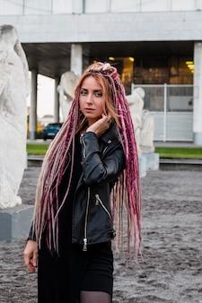Mulher jovem e bonita com longos dreadlocks rosa em um vestido preto e jaqueta de couro