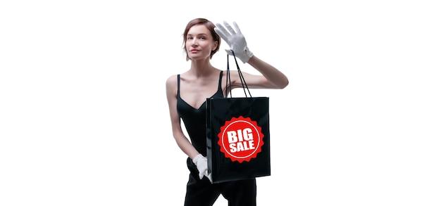 Mulher jovem e bonita com luvas brancas segurando uma bolsa artesanal preta na mão