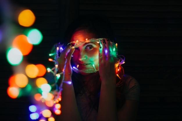 Mulher jovem e bonita com luzes garland brilhantes