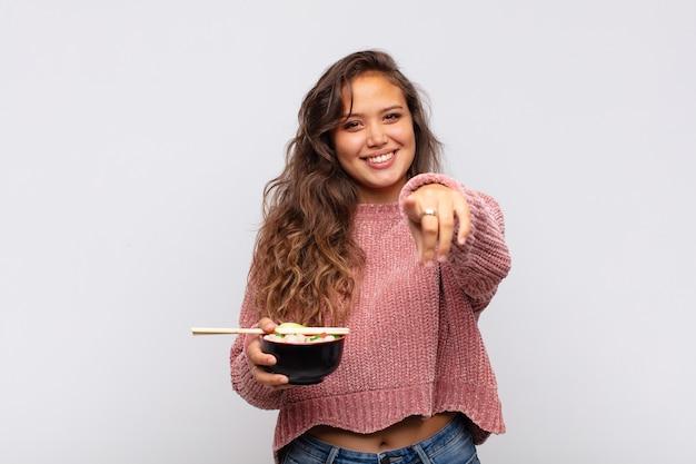 Mulher jovem e bonita com macarrão apontando para a câmera com um sorriso satisfeito, confiante e amigável, escolhendo você