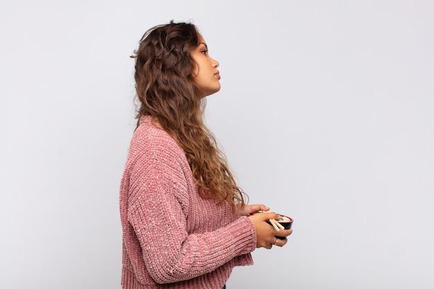 Mulher jovem e bonita com macarrão em vista de perfil, olhando para copiar o espaço à frente, pensando, imaginando ou sonhando acordada