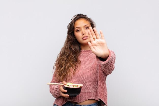 Mulher jovem e bonita com macarrão parecendo séria, severa, descontente e irritada mostrando a palma da mão aberta fazendo gesto de pare
