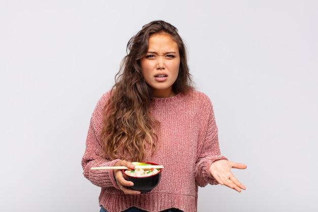 Mulher jovem e bonita com macarrão parecendo zangada, irritada e frustrada gritando wtf