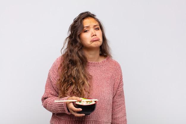 Mulher jovem e bonita com macarrão se sentindo triste e chorona com uma aparência infeliz, chorando com uma atitude negativa e frustrada