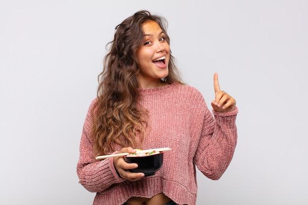 Mulher jovem e bonita com macarrão se sentindo um gênio feliz e animado depois de realizar uma ideia, levantando alegremente o dedo, eureka!