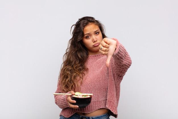 Mulher jovem e bonita com macarrão se sentindo zangada, irritada, desapontada ou descontente, mostrando os polegares para baixo com um olhar sério